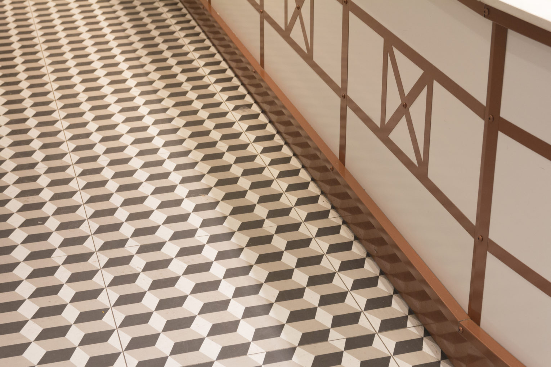 Boulangerie Pâtisserie La renaissance détail sol motif géométrique grès céram détail sous bassement cuivre conçu par Pep's création